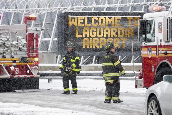 Un grupo de bomberos trabaja en el exterior del aeropuerto La Guardia de...