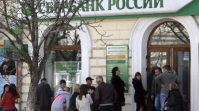 Ciudadanos crimeos esperan su turno para cambiar grivnas a rublos en una...