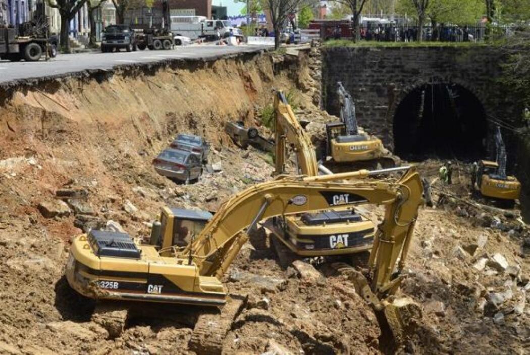 Una máquina retira tierra junto a un coches semienterrado del inmenso so...