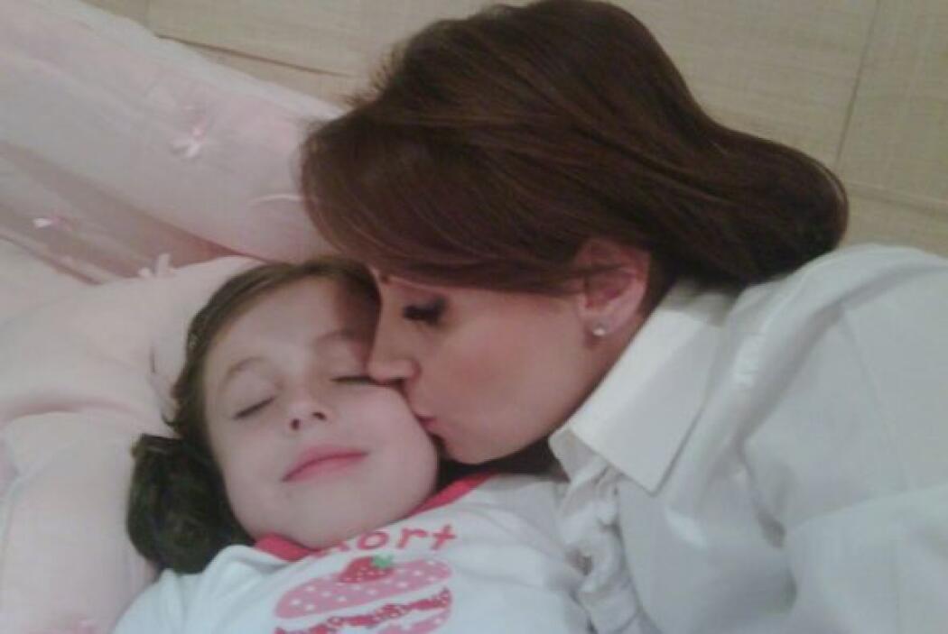 Aquí dando el beso de las buenas noches a la más pequeña de sus hijas Re...