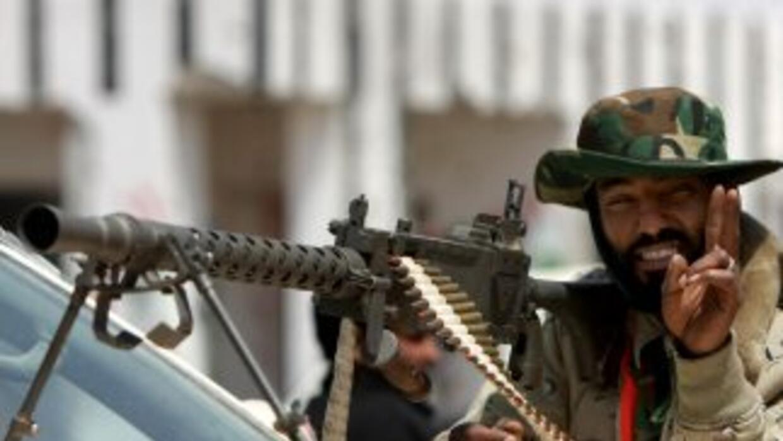 Un debelde libio hace un saludo de victoria mientras hace guardia junto...