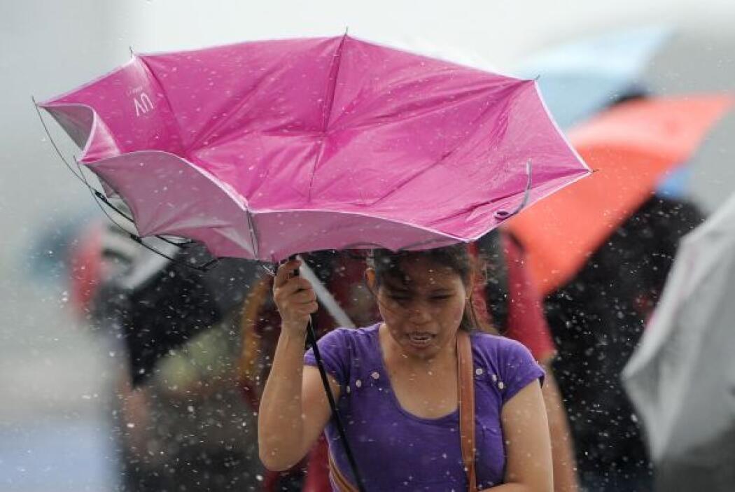 Una mujer lucha por controlar su paraguas roto mientras camina bajo la l...