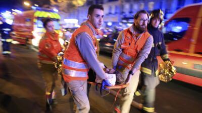 Una mujer es evacuada de la sala de conciertos Bataclan.