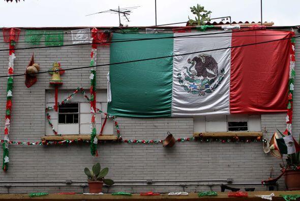 Asimismo, varias casas y comercios lucen adornados con banderas mexicana...