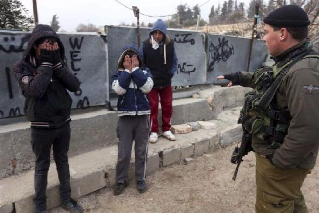 Unos soldados israelíes hablan con unos niños palestinos tras detenerles...