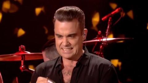Robbie Williams se desinfectó las manos después de saludar...