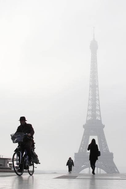 Un hombre monta una bicicleta en la explanada del Trocadero frente a la...
