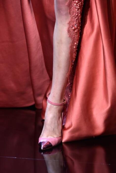 Un vestido largo con abertura en la pierna, detalles de pedrería y encaj...
