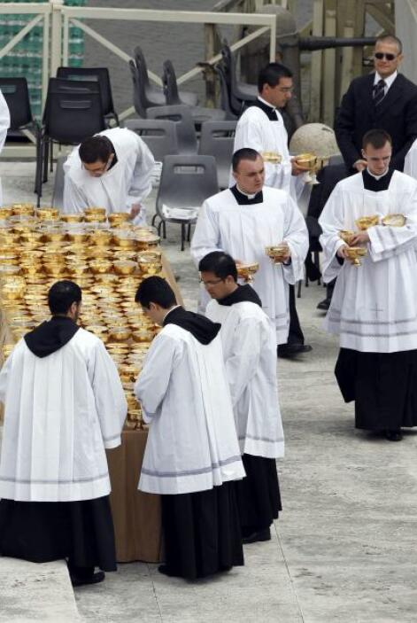Un grupo de sacerdotes se encuentra preparando los cálices para la comun...