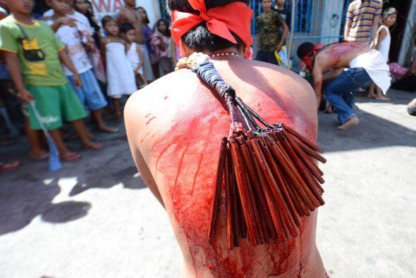 Este penitente se flagela a si mismo frente a la muchedumbre congregada...