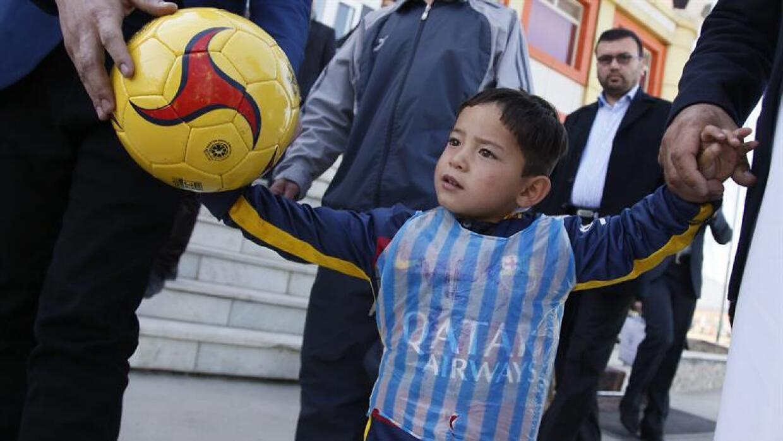 El niño afgano de 5 años Murtaza Ahmadi posa con una camiseta de su ídol...