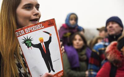 Una joven con la portada diseñada por Edel Rodríguez en una protesta con...
