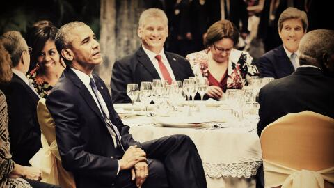 US President Obama listens to music as First Lady chats with Raul Castro.