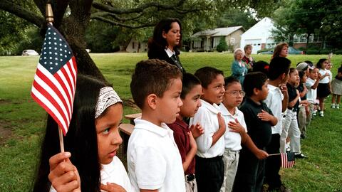 A class of Hispanic students recites the Pledge of Allegiance during a S...