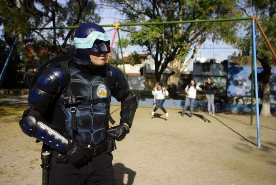 El traje de héroe de Menganno consta de una máscara azul de látex que le...