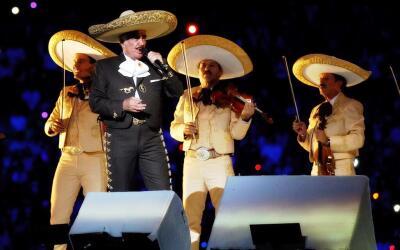 Vicente Fernández canta con mariachi sobre un escenario.