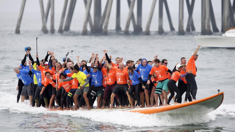 66 personas se subieron a una enorme tabla de surf para romper un récord...