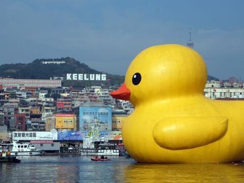 Los visitantes miran un patito de baño de 18 metros de altura que flota...