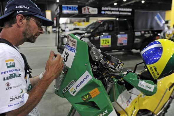 Un miembro del equipo KTM pone la identidicación en la moto del b...