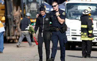 Un oficial de Alameda abraza y consuela a una mujer en la escena cerca d...