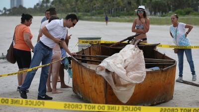 Bañistas inspeccionan un bote que llegó a Miami Beach.