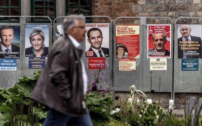 Un transeunte pasa frente a los carteles electorales de algunos de los o...
