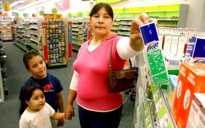 La mexicana Isabel Segovia, acompañada por sus hijos, compra medi...