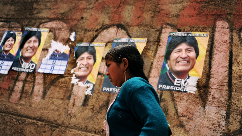 Una mujer pasa por delante de un cartel con la imagen de Evo Morales.