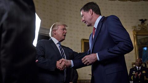 Donald Trump y James Comey se saludan el 22 de enero en un evento en la...