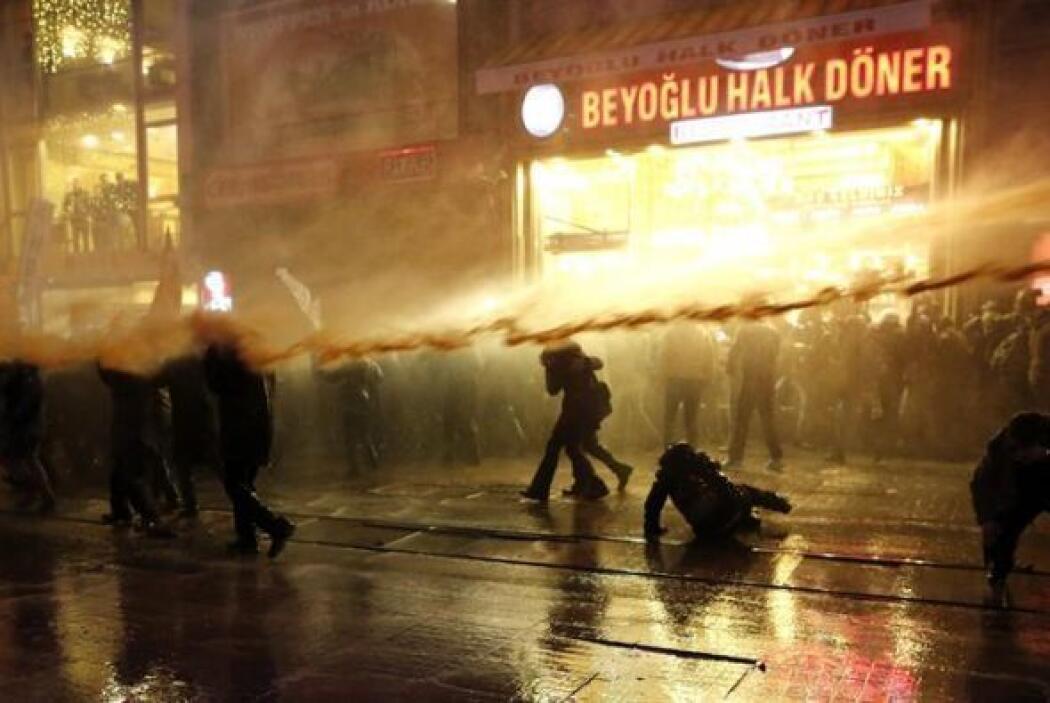 Policías antidisturbios usan un cañón de agua para dispersar a manifesta...