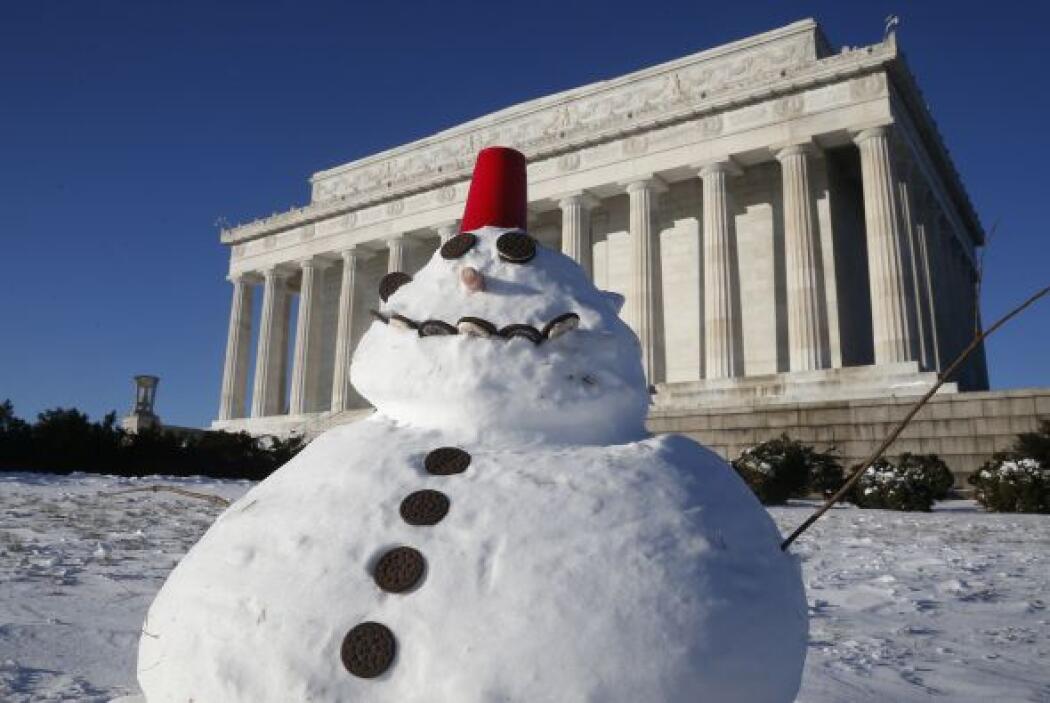 Este muñeco de nieve está adornado con galletas y una taza roja de plást...