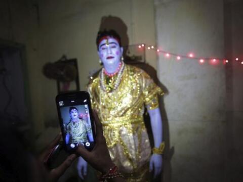 Varios hombres disfrazados como dioses hindúes se preparan para particip...