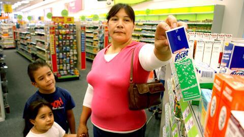 La mexicana Isabel Segovia, acompañada por sus hijos, compra medicinas e...