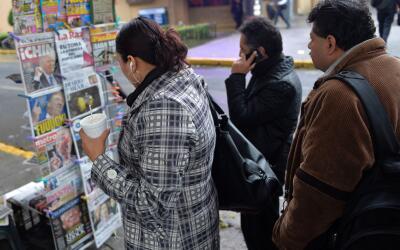 Mexicanos miran los titulares de los periódicos que dieron cuenta...