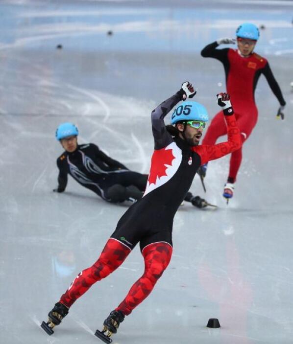 Charles Hamelin, de Canadá, celebra mientras otro de los competidores de...