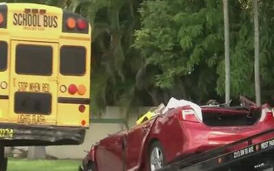 Auto incrustado bajo la parte trasera de un autobús escolar en Florida