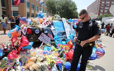 Un policía llega a visitar el 'memorial' afuera de la sede polici...