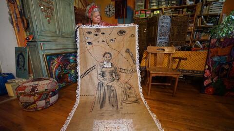 Virginia Ayress mostrando un tapiz de 10 pies de altura con la imagen de...