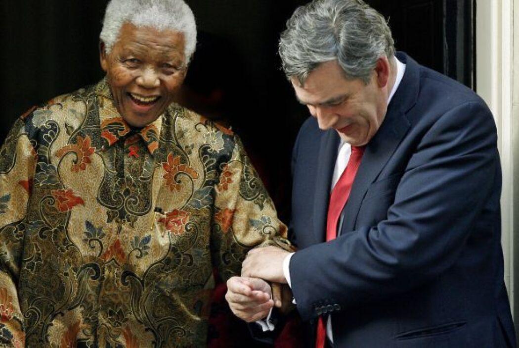 Nelson Mandela es ayudado por un paso por el primer ministro británico,...