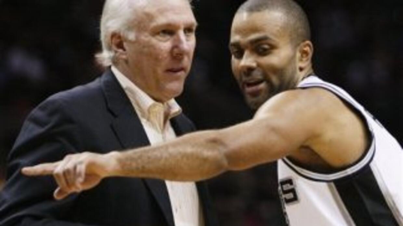 Tony Parker y su entrenador Greg Popovich hablan durante un partido de p...