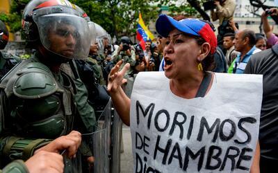 Una manifestante vocifera contra los soldados de la Guardia Nacional que...