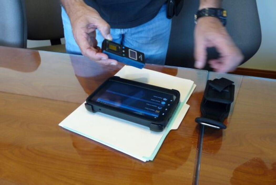 Un agente muestra la tableta que usan para sacar las fotografías y un es...