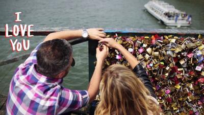 A couple locks a padlock on the 'Pont des Arts'