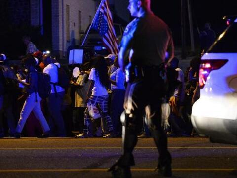 Un policía vigila a manifestantes durante otro día de prot...