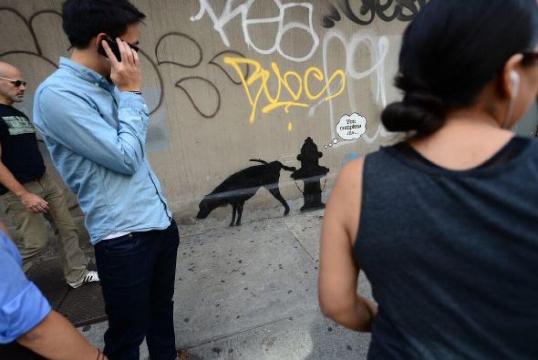 La gente mira sorprendida el arte graffiti callejero del artista británi...