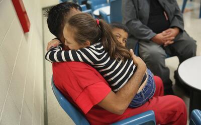 Un inmigrante indocumentado abraza a una de sus hijas en un centro de de...