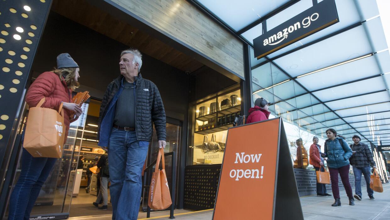 Un cliente sale de la tienda Amazon Go de Seattle, tras su inauguración...