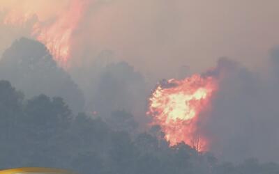 Bomberos combaten por tierra y aire un incendio forestal en las montañas...