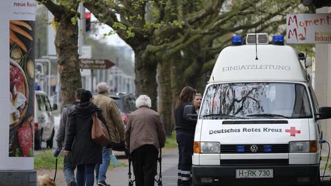 Residentes pasan junto a equipos de emergencias en Hannover-Vahrenfeld,...