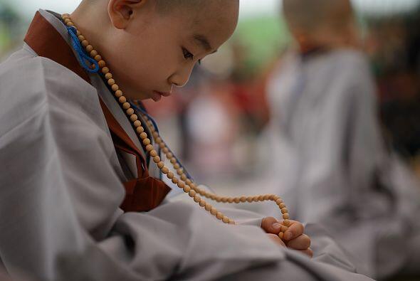 Este joven monje toma su collar religioso y lo mira con fe después del a...